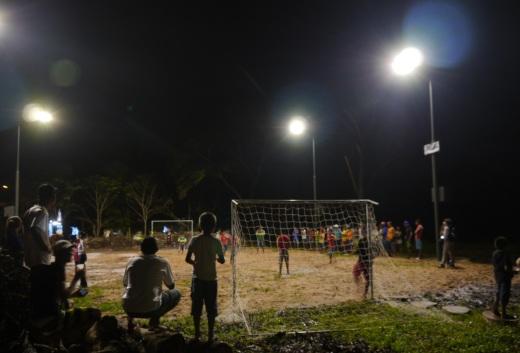 Jovens participam de partida de futebol em campo iluminado com energia solar, em Cotijuba. (foto: Eric Stoner)